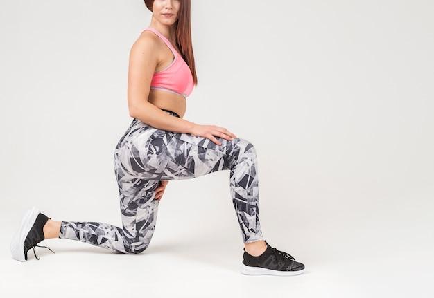 Vista laterale della donna sportiva che si siede su un ginocchio