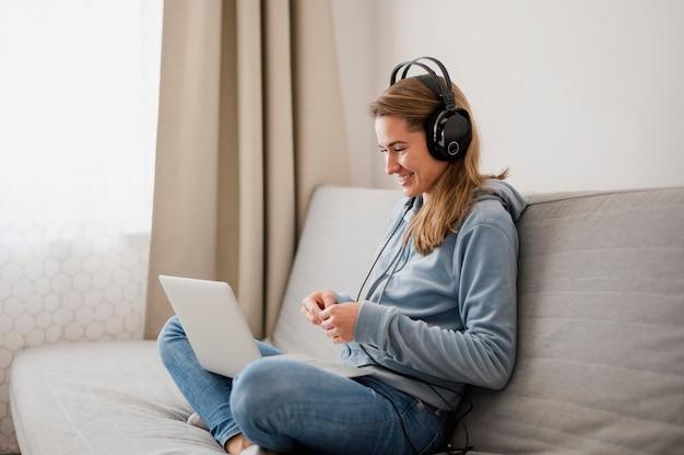 Vista laterale della donna sul divano con una classe online