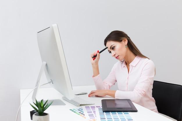 Vista laterale della donna sul lavoro che pensa e che esamina computer