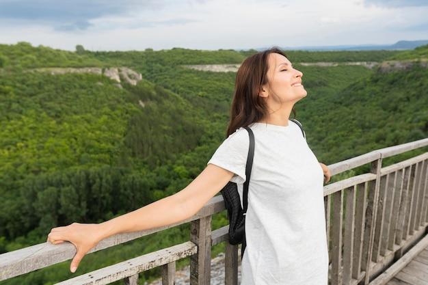 Vista laterale della donna sul ponte che gode della natura