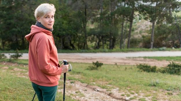 Vista laterale della donna turistica anziano con bastoncini da trekking