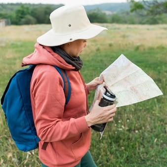 Vista laterale della donna turistica anziano con thermos e mappa