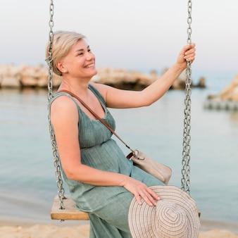 Vista laterale della donna turistica di smiley sulla spiaggia nell'oscillazione