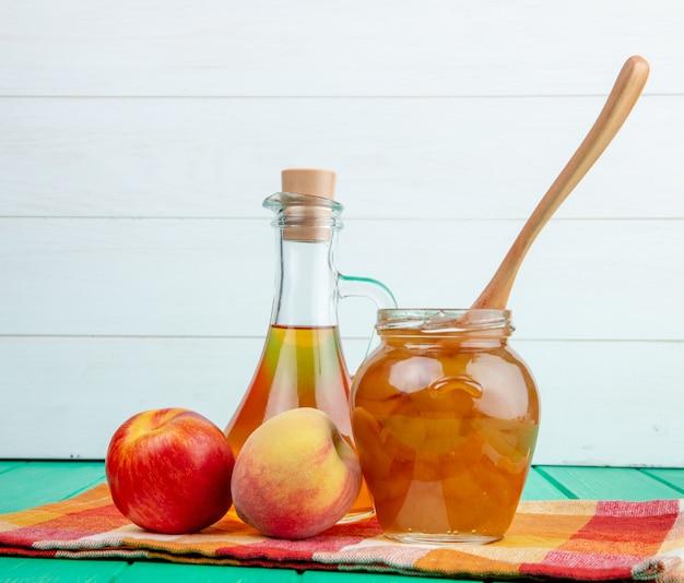 Vista laterale della frutta fresca mela con pesca e una bottiglia di olio d'oliva e marmellata di pesche in un barattolo di vetro con un cucchiaio di legno su sfondo verde in legno