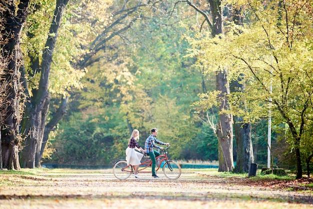 Vista laterale della giovane coppia di turisti, uomo barbuto bello e donna che guidano insieme in bicicletta doppia in tandem da vicolo soleggiato con foglie dorate su alberi ad alto fusto