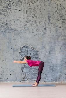 Vista laterale della giovane donna che fa allungando esercizio su sfondo grigio
