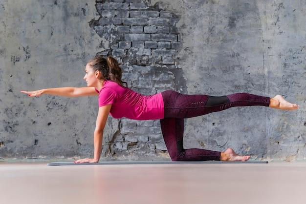 Vista laterale della giovane donna che fa esercizio del cane di uccello contro fondo grigio