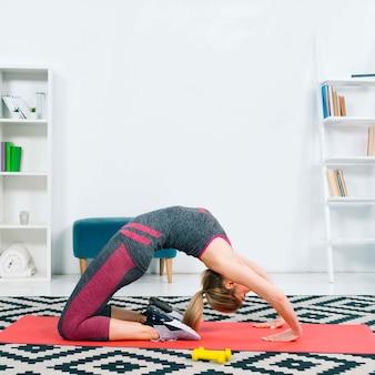 Vista laterale della giovane donna che si esercita sulla stuoia di esercizio rossa sopra il tappeto del modello a casa