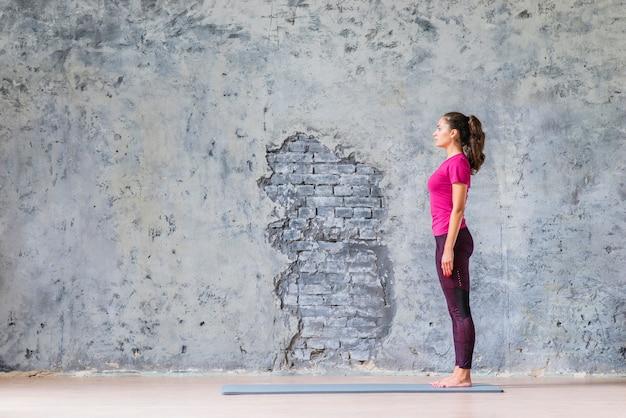 Vista laterale della giovane donna che sta sulla stuoia di esercizio contro la parete stagionata grigia