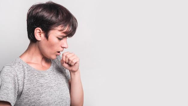 Vista laterale della giovane donna che tossisce contro fondo grigio