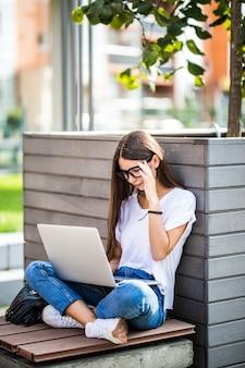 Vista laterale della giovane donna in occhiali seduto sulla panchina nel parco e utilizzando il computer portatile