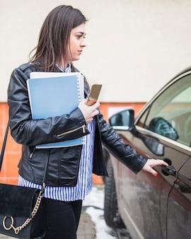 Vista laterale della giovane porta di automobile di apertura della donna di affari