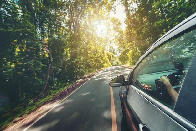 Vista laterale della guida di veicoli sulla strada in autostrada forestale