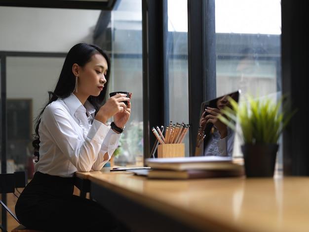 Vista laterale della lavoratrice fare una pausa caffè mentre lavora online nella caffetteria