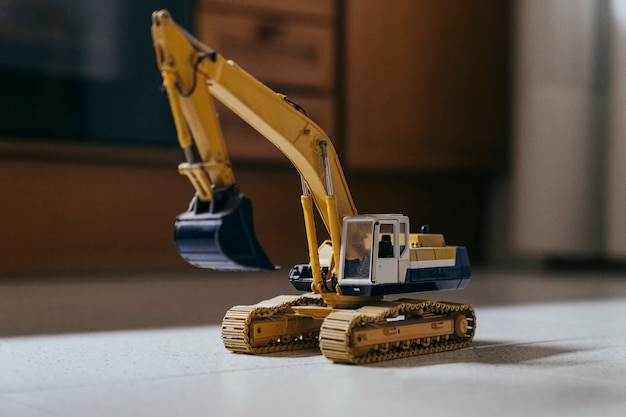 Vista laterale della macchina del giocattolo dell'escavatore in un pavimento delle cucine