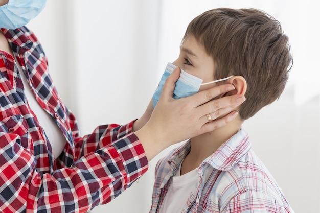 Vista laterale della madre che mette maschera medica sul bambino
