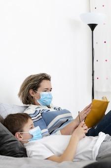 Vista laterale della madre e del bambino a letto indossando maschere mediche