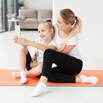 Vista laterale della madre e della figlia che prendono selfie sulla stuoia di yoga