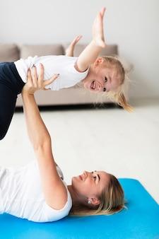 Vista laterale della madre sulla stuoia di yoga che alza figlia felice