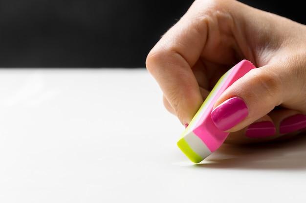 Mano che cancella con una gomma da matita | Foto Premium