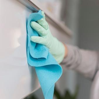 Vista laterale della mano con la superficie di pulizia dei guanti con un panno