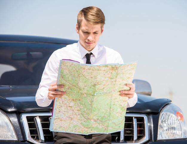 Vista laterale della mappa della lettura dell'uomo d'affari oung.