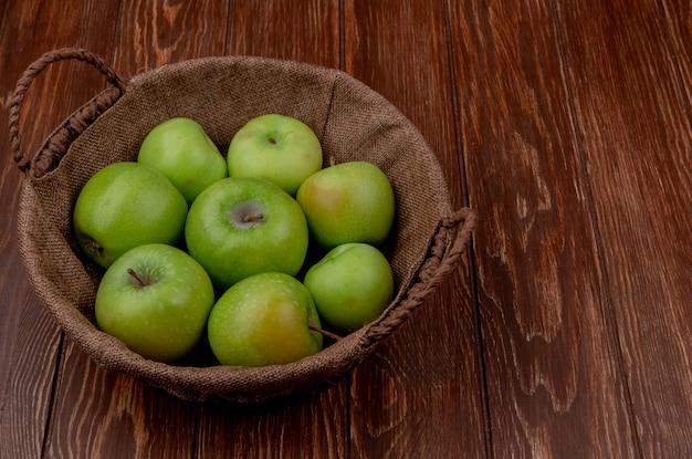 Vista laterale della merce nel carrello verde delle mele su superficie di legno con lo spazio della copia