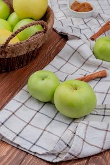 Vista laterale della merce nel carrello verde e gialla delle mele con la marmellata di mele e cannella e mele sul panno del plaid e sulla superficie di legno