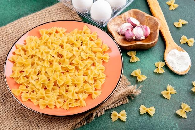 Vista laterale della pasta cruda su un piatto con uova all'aglio e un cucchiaio di farina su una superficie verde