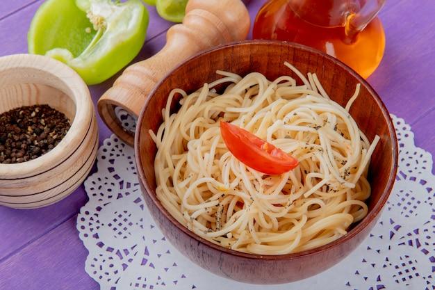 Vista laterale della pasta degli spaghetti in ciotola sul centrino di carta con mezzo sale pepe burro nero e pepe nero sulla superficie viola