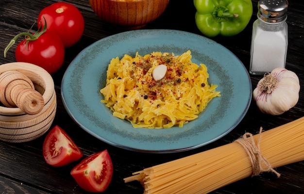 Vista laterale della pasta di maccheroni in zolla con aglio e vermicelli del frantoio dell'aglio del sale del pepe dei pomodori sulla tabella di legno