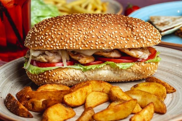 Vista laterale della patata casalinga del pomodoro della cipolla del formaggio della lattuga del panino del pollo