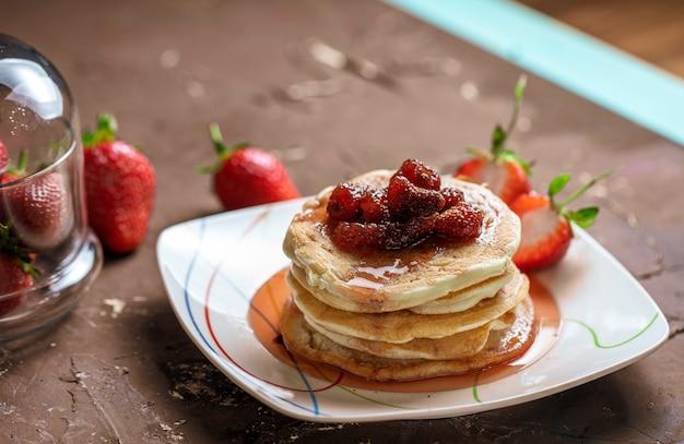 Vista laterale della pila di pancake fatti in casa con marmellata di fragole su un piatto e fragole fresche su rustico