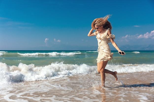 Vista laterale della ragazza allegra che gioca con le onde sulla spiaggia sabbiosa