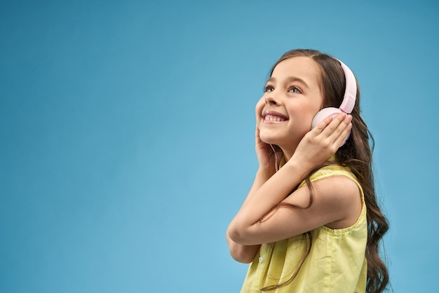 Vista laterale della ragazza allegra nella musica d'ascolto delle cuffie