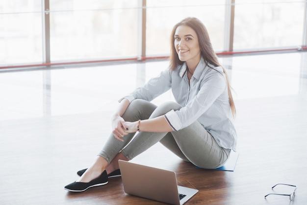 Vista laterale della ragazza attraente che utilizza un computer portatile nell'area pubblica di wifi e che sorride mentre sedendosi sul pavimento