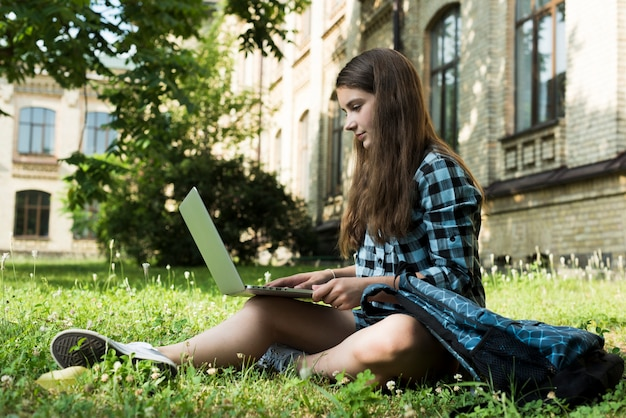 Vista laterale della ragazza della scuola utilizzando il computer portatile