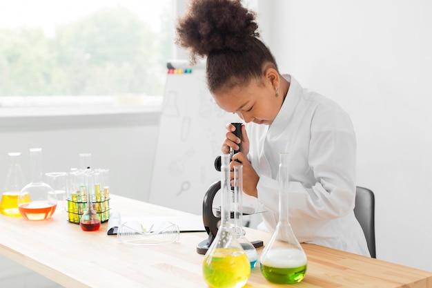 Vista laterale della ragazza in camice da laboratorio guardando attraverso il microscopio