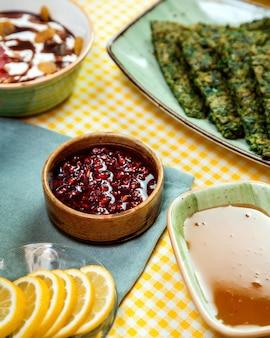 Vista laterale della salsa di melograno in ciotola ed e miele sul tavolo