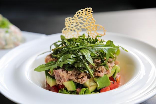 Vista laterale della salsa di ruccola del cetriolo dell'avocado del pomodoro dell'insalata di tonno