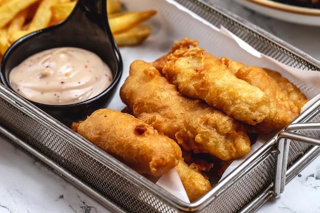 Vista laterale della salsa e delle patate fritte del witg delle dita del pollo fritto