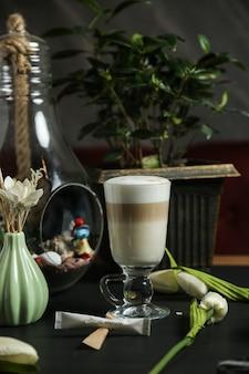 Vista laterale della schiuma del latte alla cannella del caffè espresso del latte del caffè nero del latte