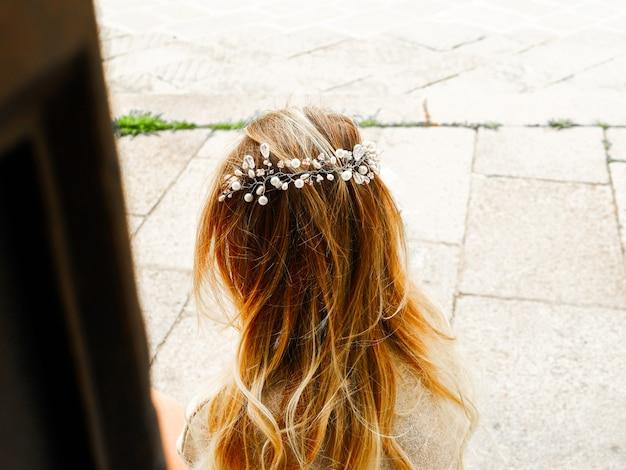 Vista laterale della sposa moderna in acconciatura decorata da accessori per capelli in rilievo fantasia. concetto di matrimonio capelli. corona di cristallo su capelli mossi. copia spazio