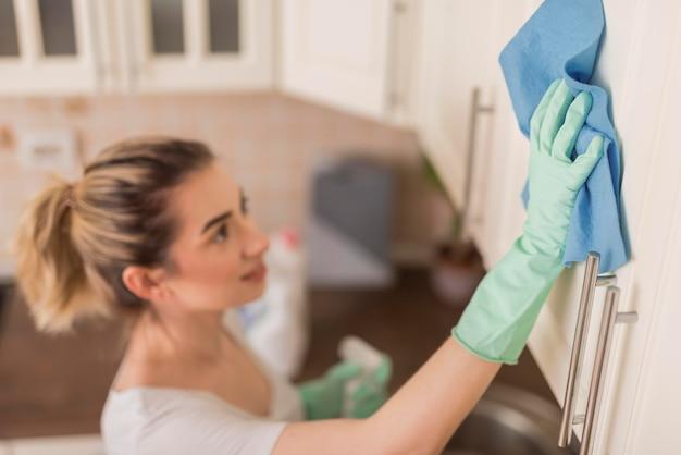 Vista laterale della superficie di pulizia della donna con il panno nella cucina