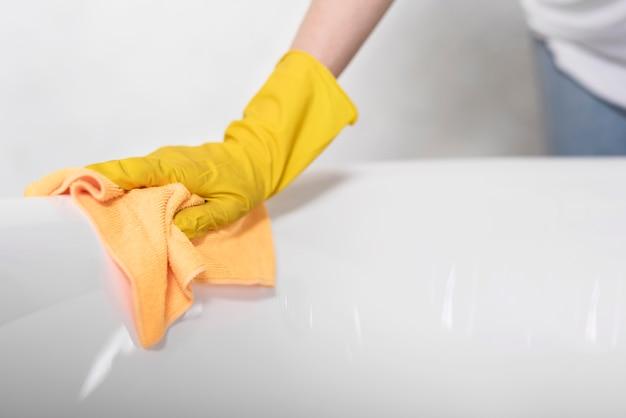 Vista laterale della superficie di pulizia della donna con il panno