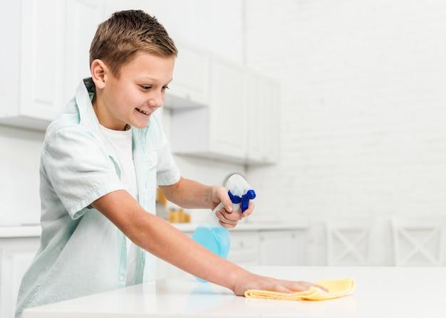 Vista laterale della tabella felice di pulizia del ragazzo con lo straccio