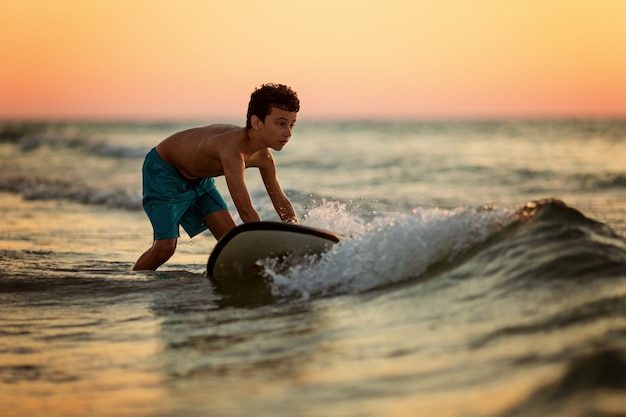 Vista laterale della tavola da surf di galleggiamento del bambino impavido all'oceano con le onde sulla sera soleggiata
