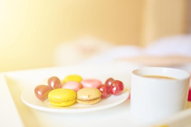 Vista laterale della tazza di caffè con gustosi macarons colorati o amaretti sul vassoio bianco