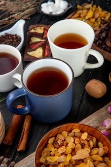 Vista laterale della tazza di tè con l'uva passa secca in una ciotola di legno su rustico
