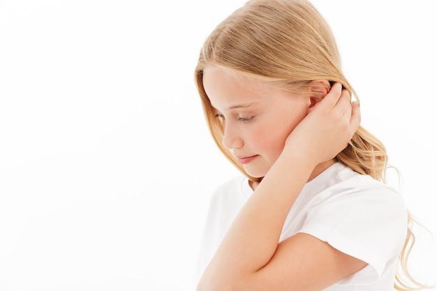 Vista laterale della timida giovane ragazza bionda in abiti casual, toccando i suoi capelli e guardando in basso sul bianco
